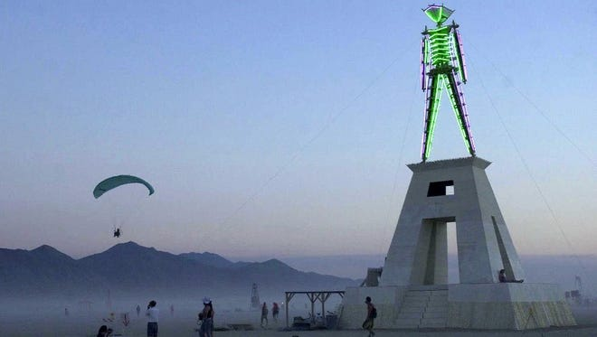 In 2005: Burning Man participants stand under the Man in the Black Rock Desert.