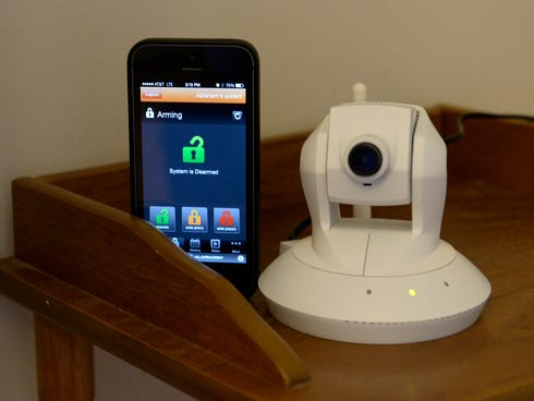 A mobile app and a pan-and-tilt security camera are parts of an Alarm.com home system.