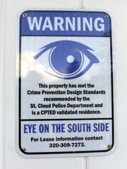 A large sign outside the door of a rental home pictured in 2015 warns that the home is one that participates in the Eyes on the South Side program.