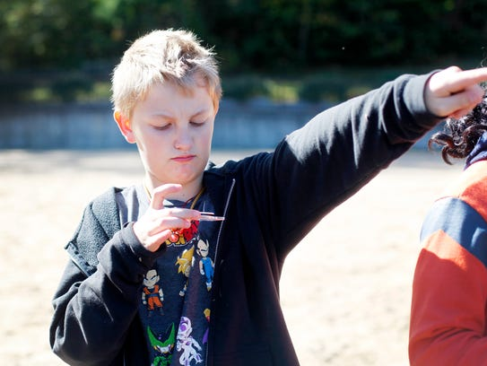 Porter Howerter, 10, points north as he learns how