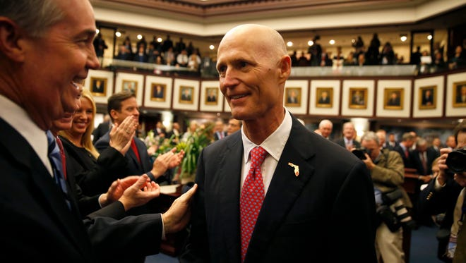 Gov. Rick Scott makes his way to the head of the House of Representatives chamber to give his State of the State address during the first day of the legislative session on Tuesday, Jan. 12, 2016.