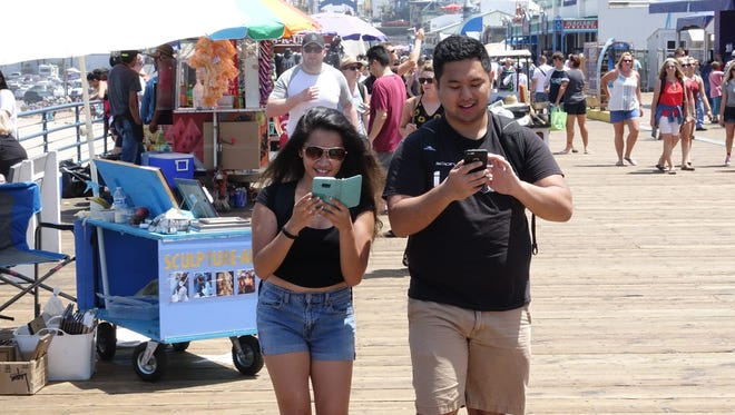 UCLA students Jessica Cantiller, 22 and  Adrian Navarro, 21, play Pokemon Go on the Santa Monica Pier.