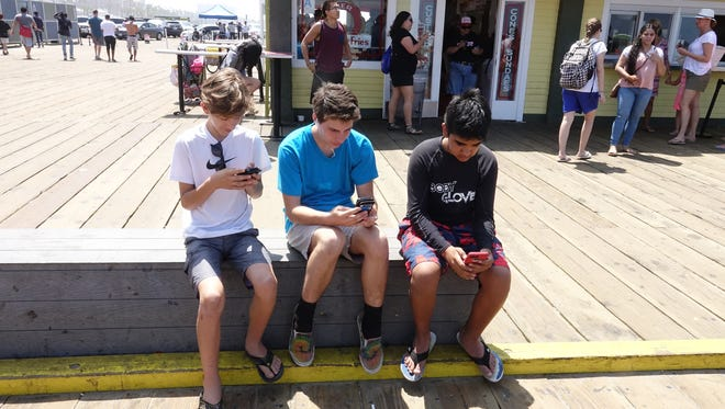 Brothers Lance and Max Santana and Ryan Reinoso play Pokemon Go at the Santa Monica Pier.