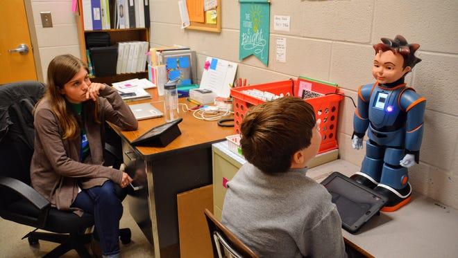 Milo, far right, is a humanoid robot that helps students with autism develop social skills.  Special education teacher Megan Vranicar,  far left, chooses the lesson for Poplar Grove Middle School student Caleb McCeney.