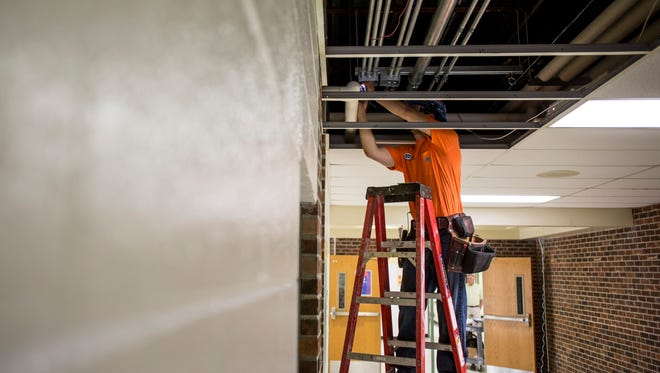 A contractor works on installing lines for a fire system Thursday, May 18, 2017 at Holland Woods Middle School in Port Huron.