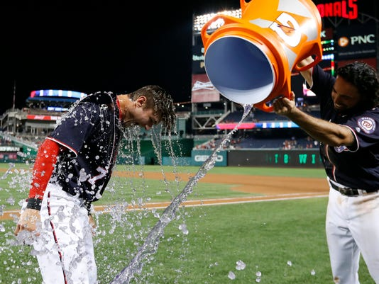 Washington Nationals' Trea Turner, left, reacts after being doused by Anthony Rendon following a baseball game against the Philadelphia Phillies at Nationals Park, Friday, Sept. 9, 2016, in Washington. Turner hit the game-winning walk off home run as the Nationals won 5-4. (AP Photo/Alex Brandon)