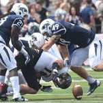Nevada's Brandon Thompson, left, Duran Workman and Austin Fletcher team up to force a fumble from Southern Utah's Chandler Allphin on Saturday.