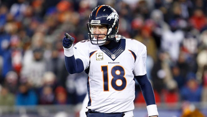 Denver Broncos quarterback Peyton Manning (18) points to the bench in the first quarter against the New England Patriots at Gillette Stadium.