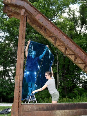 Oliver and Miranda Clark hang various colors of materials on sections of the steel bridge display that once spanned Hinkson Creek when the train traveled the MKT Trail east of Scott Boulevard.