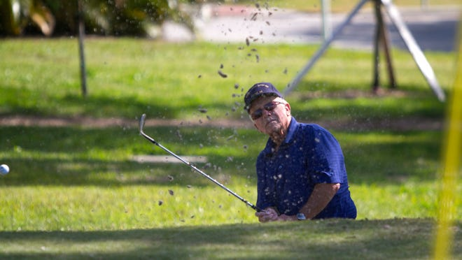 George Grohs hits a shot out of the sand trap on Friday at Fort Myers Country Club.