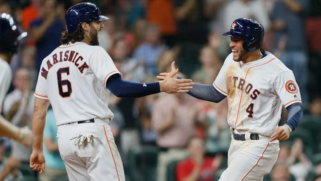George Springer (4) slaps the hand of Jake Marisnick after scoring in the sixth inning of the Astros' win over the Mariners.