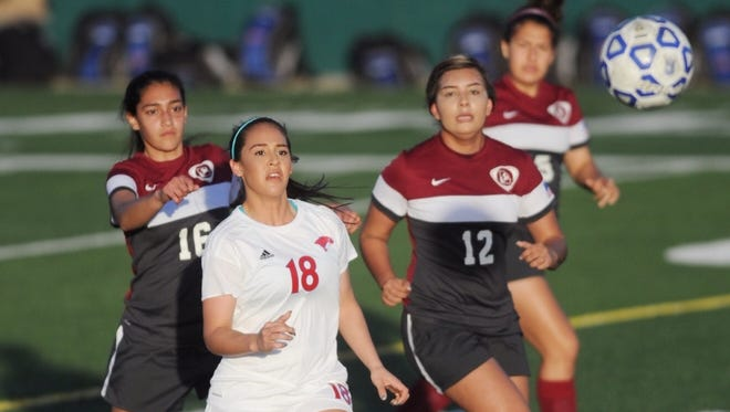Cooper's Judith Macias (18) chases the ball along with Midland Lee's Andrea Olivas (12), Tatiana Sandoval (16) and another Lady Rebel. Cooper beat the Lady Rebels 2-1 in a nondistrict girls soccer game Tuesday, Jan. 24, 2017 at Shotwell Stadium.