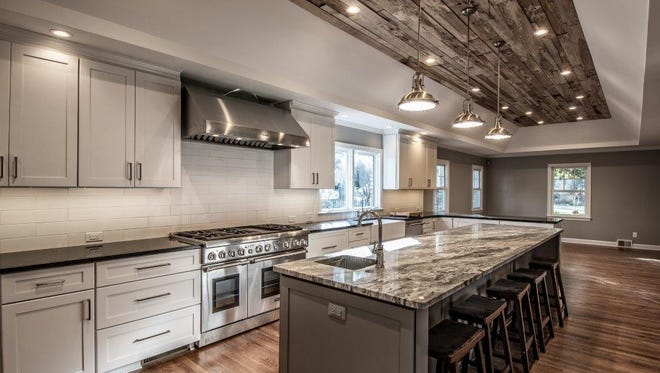 This kitchen renovation took down a wall separating the dining room behind it and raised the ceiling. This reclaimed wood ceiling is the focal point of this 38 x 15 room.
