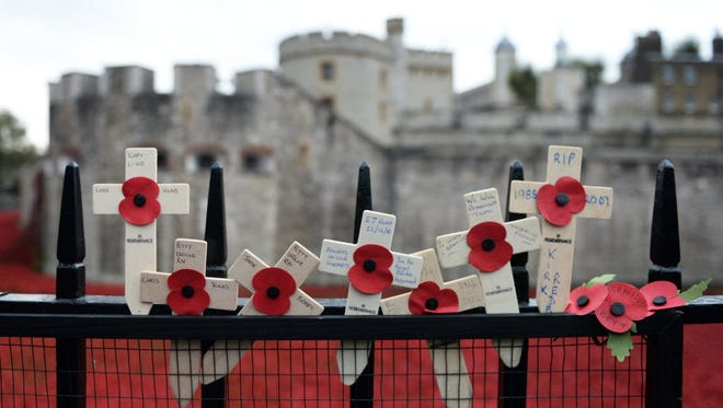 Wooden crosses are placed on the last day of the Tower of London's 'Blood swept Lands and Seas of Red' poppy installation in the Tower of London in London, Britain, 11 November 2014.