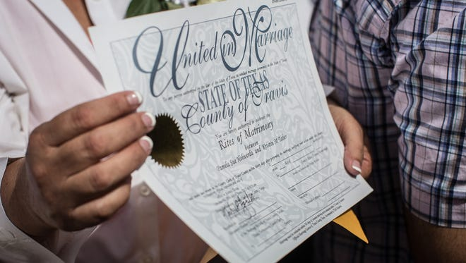 Pamela Holwerda holds up her marriage license following the ceremony that married over 40 same-sex couples on the south lawn of the Texas State Capitol in Austin on July 4, 2015.