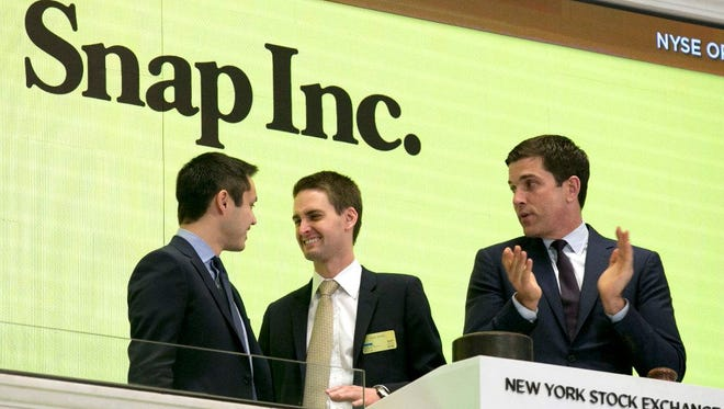 Snapchat co-founders Bobby Murphy, left, and CEO Evan Spiegel, center, ring the opening bell at the New York Stock Exchange as the company celebrates its IPO on March 2, 2017.