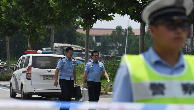 Police officers carry equipment outside a kindergarten where an explosion killed 8 people and injured dozens a day earlier, in Fengxian, in China's eastern Jiangsu province.