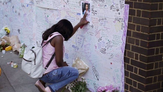 A woman touches a missing poster for 12-year-old Jessica Urbano on a tribute wall after laying flowers on the side of Latymer Community Church next to the fire-gutted Grenfell Tower in London on June 16.
