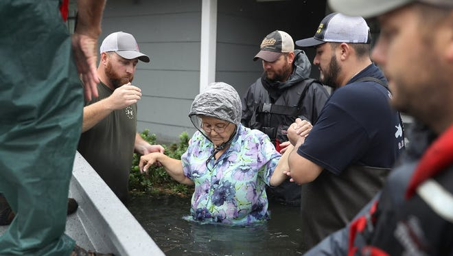 Volunteer rescuers help a woman from her inundated home after Hurricane Harvey in Port Arthur, Texas, on Aug. 30, 2017.