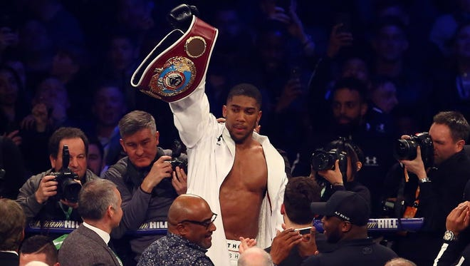 Anthony Joshua celebrates after beating Joseph Parker in their unifying heavyweight championship title bout at Principality Stadium in Wales.