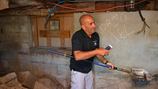 Armed with a shovel, owner Alfredo Hernandez shows where water is leaking into a crawlspace behind the utility room at El Ambia Cubano in downtown Melbourne.