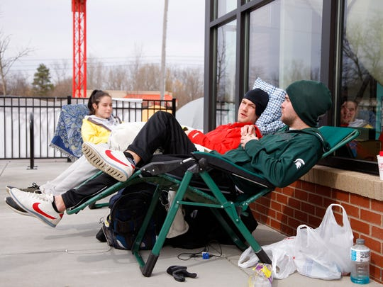 Madison Graham, left, and brothers Jordan Borchard, center, and Travis Borchard wait for the Chick-fil-A opening, Wednesday, March 29, 2017, in Okemos, Mich.