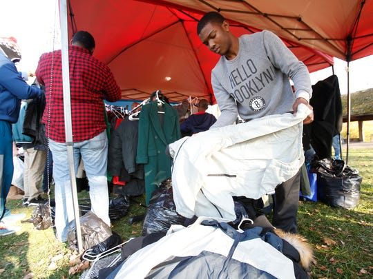 Ismail Sabir with the Noel Roberts Foundation organizes coats in the clothing giveaway portion of  Wilmington's Day of Thanks & Giving in Christina Park Saturday.