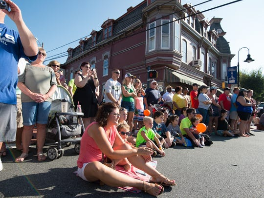 Festival goers watch the morning parade at the Middletown