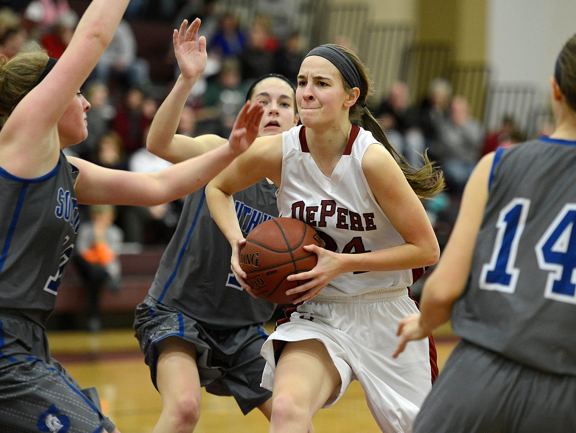 De Pere's Jessie Rabas tries to get by several Green Bay Southwest defenders while driving to the basket in a January game at De Pere High School.