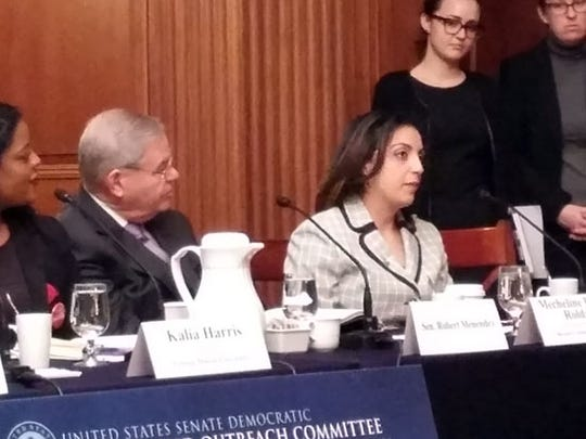 Bergen Community College professor Mecheline Farhat Roldan, seated next to New Jersey Sen. Bob Menendez, descrbies the $170,000 in student loan debt that she and her husband have during a roundtable discussion on college costs held by the Senate Democratic Steering and Outreach Committee in the Capitol on Wednesday.