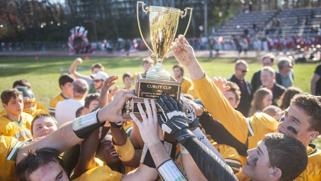 Audubon's football team in 2015 raises the Curley Cup, named for former Green Wave and Haddon Twp. coach Tom Curley. The two rivals play for it each year, this time for the first occasion since Curley passed away in September.