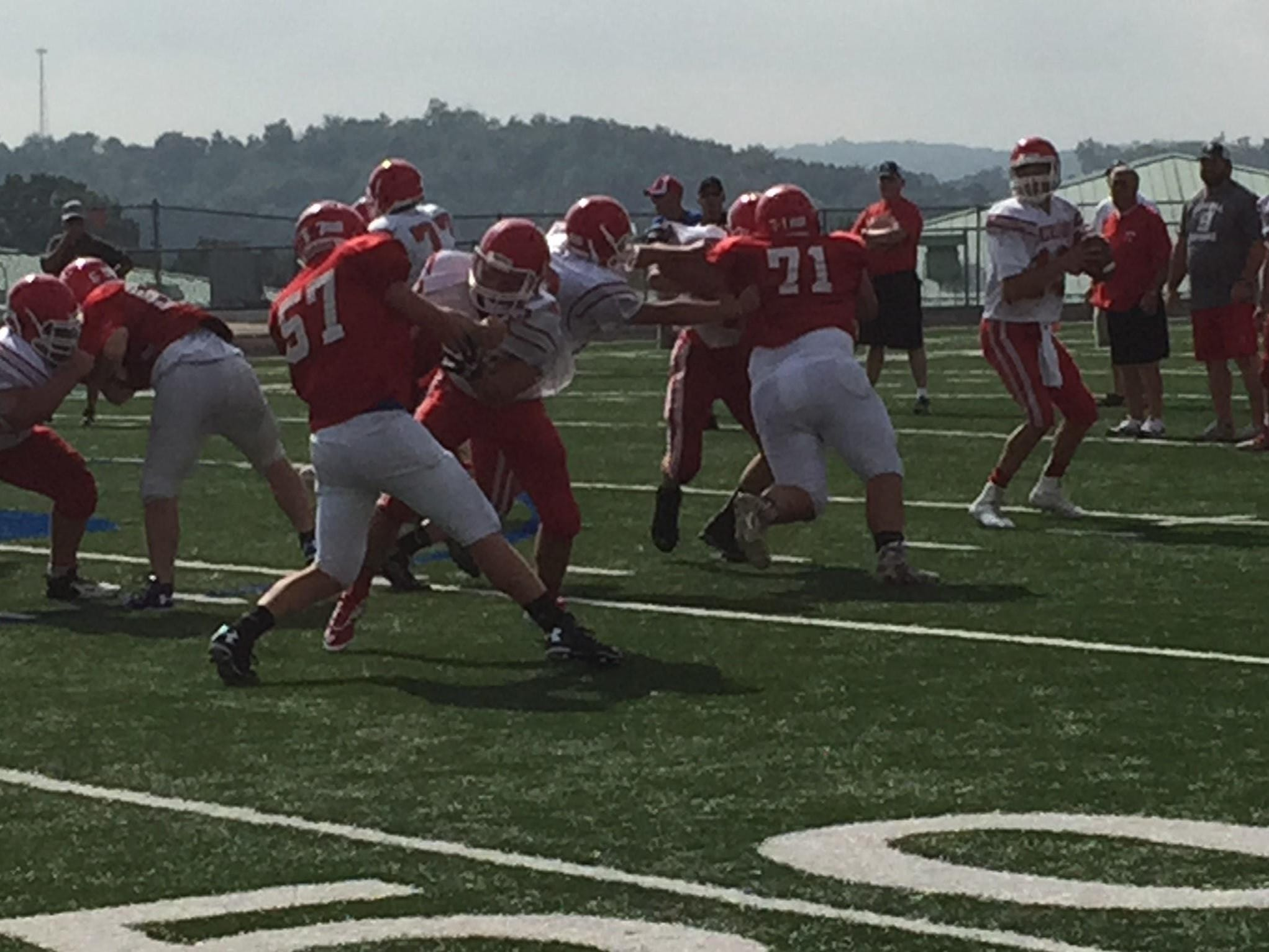 Licking Valley's Jaqui VanMeter (71) gets double-teamed as he pressures Sheridan quarterback Dylan Dupler during Tuesday's scrimmage at Randy Baughman Stadium.