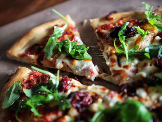 The Artist Pizza at the Midtown Crossing Grill is a fresh baked red sauce pizza with tomato jam, mozzarella and goat cheese, caramelized onion, topped with fresh arugula.