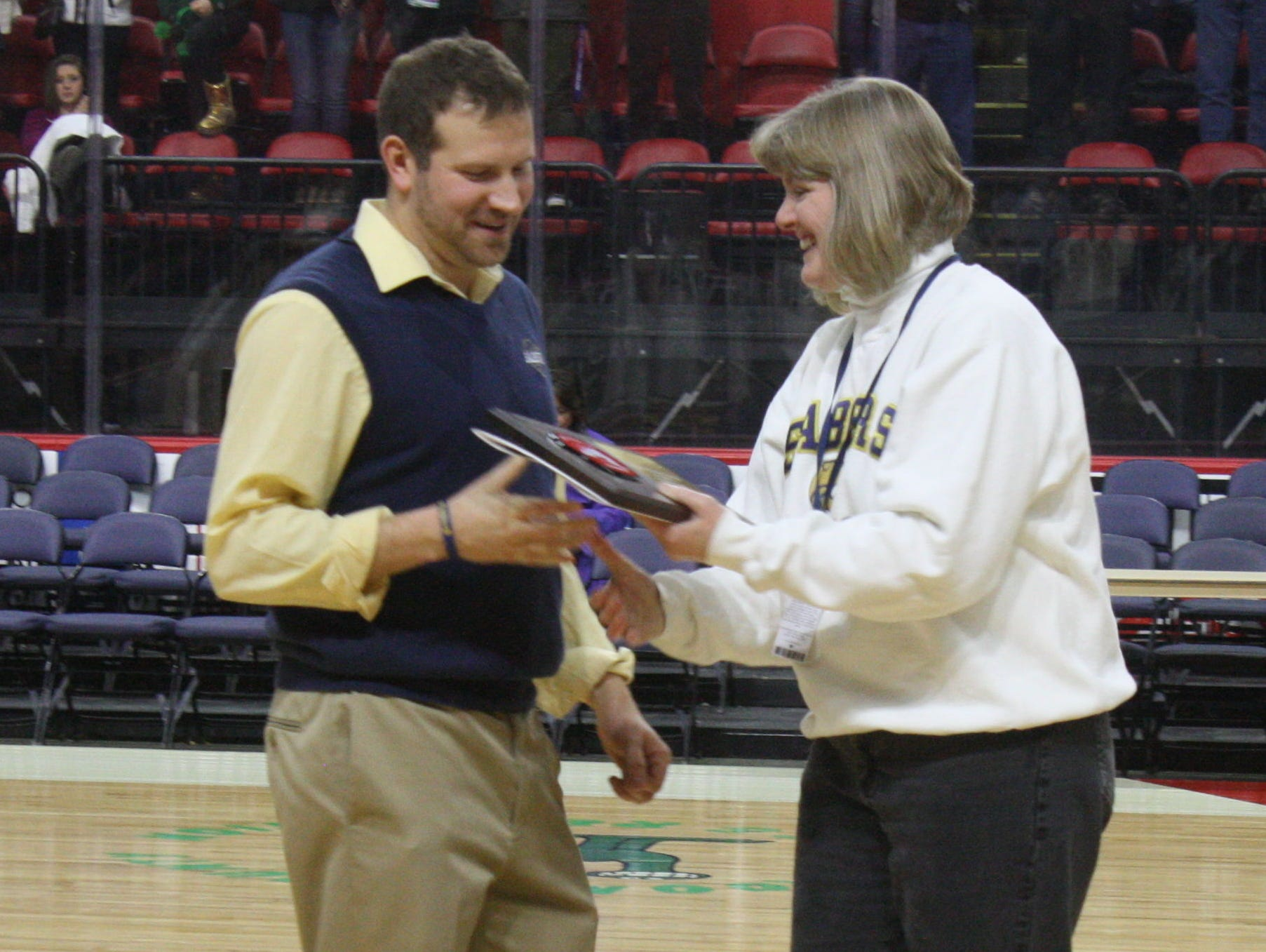 Susquehanna Valley girls basketball coach Chad Freije accepts the Section 4 Class B championship plaque from Athletic Director Denise Wickham following the Sabers' 55-49 victory on March 7.