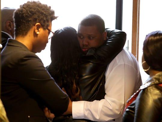 Juwan Plummer, 19, of Oak Park is consoled by friends