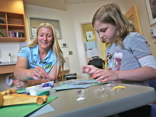 IndyCar driver Pippa Mann, left, talks with Willow Allen, 8, while they paint race car art at Riley Hospital for Children at IU Health on Monday. Mann visited with transplant patients, like Willow, as part of Donate Life Month. IndyCar driver Pippa Mann, left, talks with Willow Allen while they paint race car art at Riley Hospital for Children at IU Health, Monday, April 16, 2018.  Mann visited with several transplant patients, like 8-year-old Willow, and other patients at the hospital, as part of Donate Life Month.  Willow received a successful liver transplant on Feb. 18, 2018, at Riley Hospital, just nine days after being put on the wait list.  She is now an outpatient.