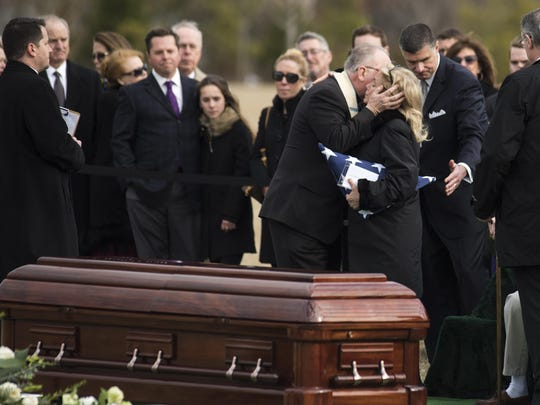 Rep. Debbie Dingell, D-Mich., is hugged by Patrick Conroy, the chaplain of the House of Representatives, during the burial services of her husband, former Rep. John Dingell, D-Mich., at Arlington National Cemetery on Friday, Feb. 15, 2019 in Arlington, Va.