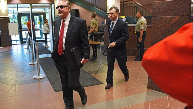 Attorney Leo Flynn walks into the Minnehaha County Courthouse with former Sioux Falls Fire Chief Jim Sideras for a court appearance Thursday, May 25, 2017, in downtown Sioux Falls. Sideras pleaded not guilty to child pornography charges during his initial appearance Thursday.