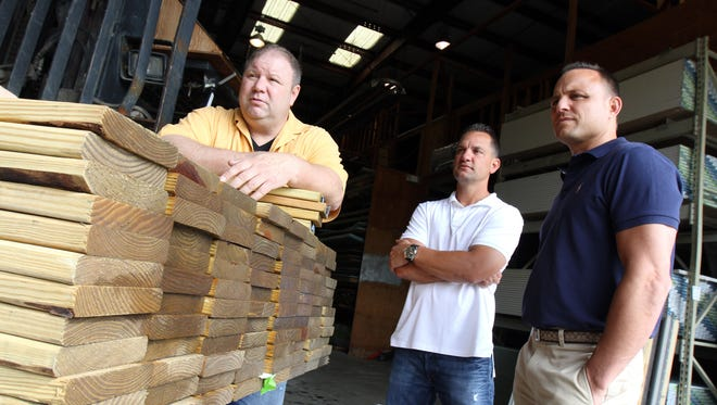 (L-R) Robert Morgenroth, manager of Park Union Building Supplies, Michael Colaiacovo and Todd Sawyer, both owners of Eastern Contractor Services and the new owners of Park Union Building Supplies, talk about the future of the business in the warehouse of Park Union Building Supplies in Randolph, NJ Wednesday July 16, 2014.