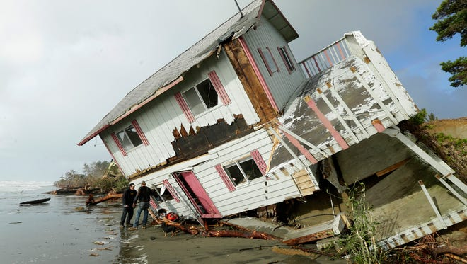 People stand next to a house that toppled over the eroding ocean shoreline of North Cove, Wash. on Friday, Dec. 12, 2014. Stormy weather blew out of Washington state on Friday, but left houses in the area listing and waves continuing to lap against sandy embankments. (AP Photo/Ted S. Warren)