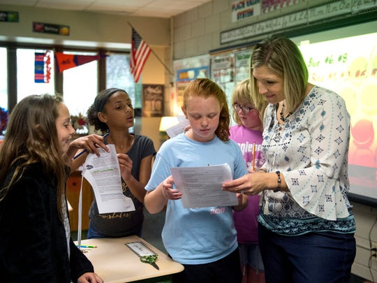 Angie Wright helps student Madison Hicks, center, during a social studies lesson about Marco Polo in her 5th grade class at Sharon Elementary School in Newburgh, Ind., on Wednesday, Oct. 4, 2017.