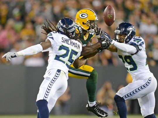Green Bay Packers receiver Ty Montgomery (88) tries to catch a pass between Richard Sherman (25) and free safety Earl Thomas (29) against the Seattle Seahawks at Lambeau Field.