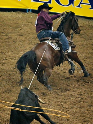 Erich Rogers competes in the team roping event on Thursday during the eighth go-round of the National Finals Rodeo in Las Vegas.