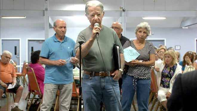 Covered Bridge resident Chuck Roden questions tax officials during a meeting at the community's clubhouse in Manalapan .