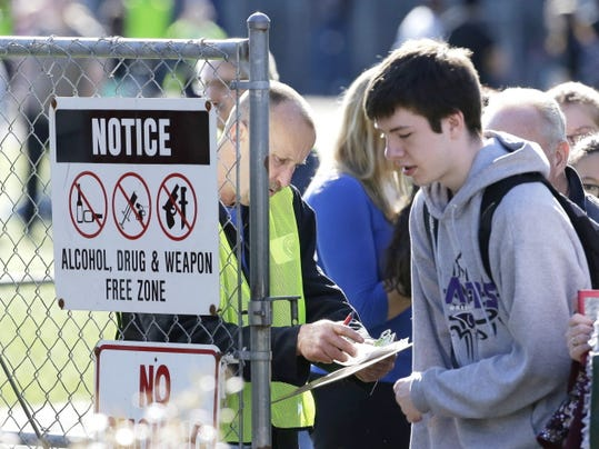 School and other officials check names and release students to parents at a gate at North Thurston High School Monday, April 27, 2015, after a shooting at the school earlier in the morning. Police say no one was injured, and school district officials say the gunman has been apprehended by staff.