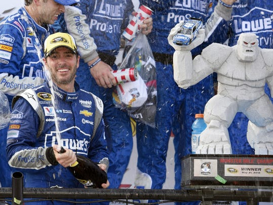 Jimmie Johnson sprays sparkling wine while celebrating in Victory Lane after he won the NASCAR Sprint Cup series auto race on Sunday at Dover International Speedway in Dover, Delaware.