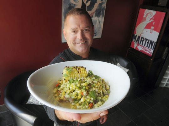 David Albright, chef and owner of the Left Bank, holds a charred sweet corn salad in the York city restaurant..
