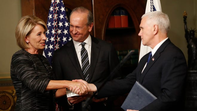 Vice President Mike Pence shakes hands after swearing in Education Secretary Betsy DeVos in the Eisenhower Executive Office Building in Washington, D.C., on Tuesday, Feb. 7, 2016, as DeVos' husband Dick DeVos watches.