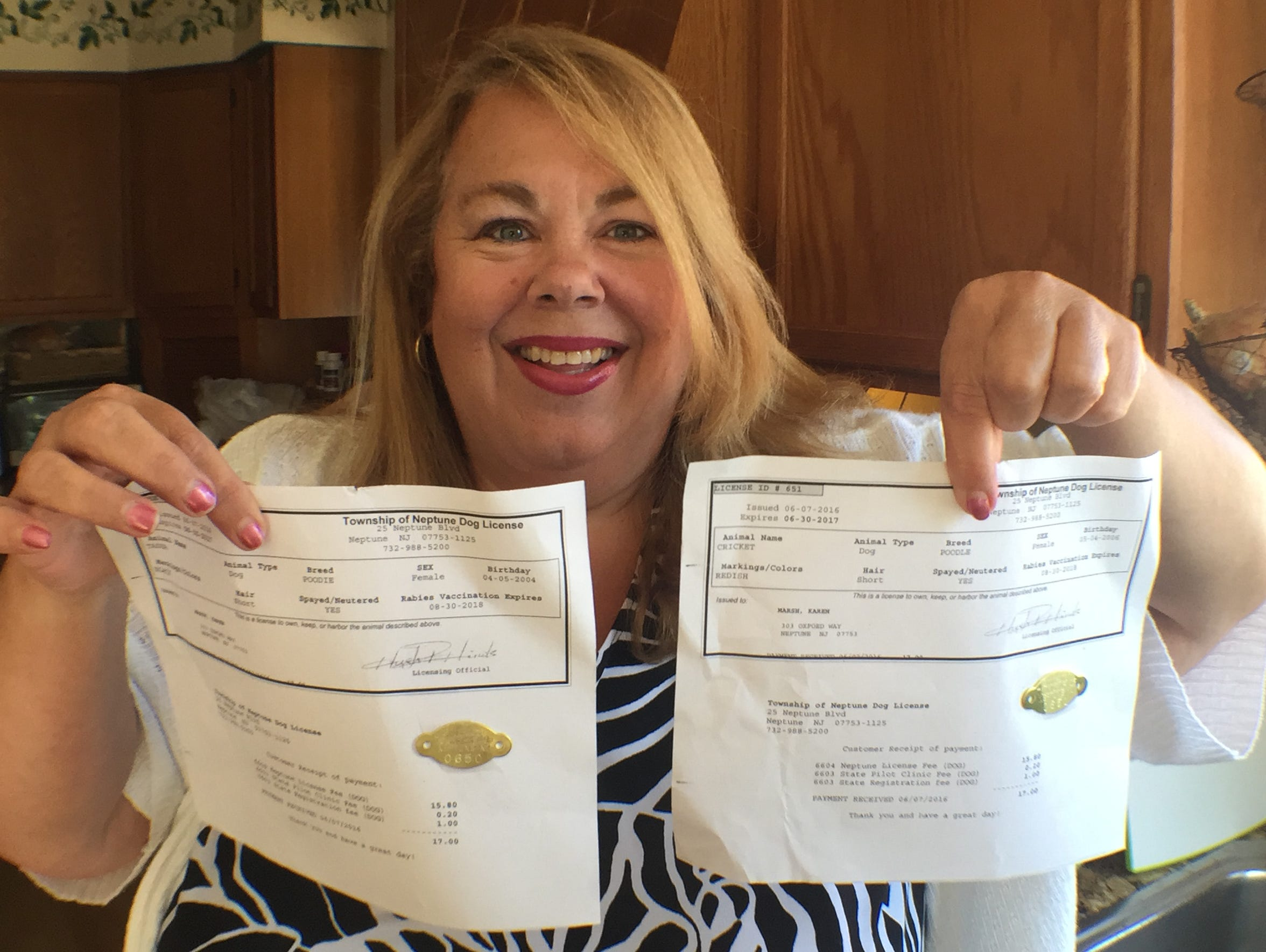 Karen Marsh, of Neptune, holds up the dog licenses