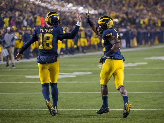 Michigan's Karan Higdon, left, celebrates a touchdown
